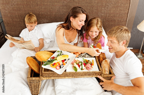 family having breakfast in bed - boy reading newspaper