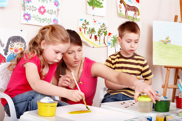 Children painting with teacher.