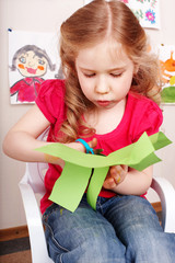 Child with scissors cut paper at home.