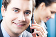 Businessman with cellphone and colleague, at office