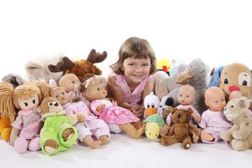 Mädchen mit Puppen und Kuscheltieren