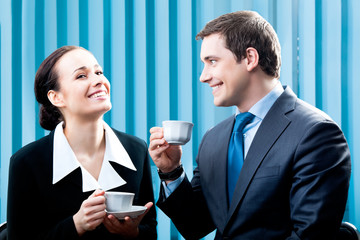 Two happy businesspeople with coffee at office