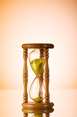Time concept - hourglass against the gradient background