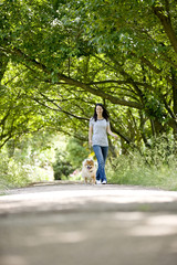 A young woman walking her dog in summertime