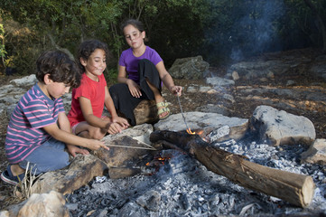 three kids in a campfire
