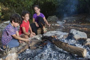 three kids in a campfire