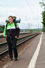 Backpacker a young woman waiting train on railway station