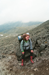 Young tired woman backpacker in mountains