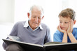 Grandfather and his grandson reading a story book