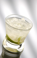 Glass of caipiriniha in front of light background
