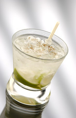 Glass of caipirinha with straw in front of a light background