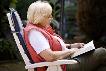 ältere Frau liest ein Buch im Garten