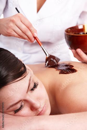 Girl having chocolate body mask .