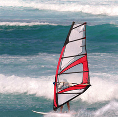 Female windsurfer in heavy waves
