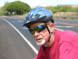 Athletic senior man riding a bicycle wearing a blue helmet