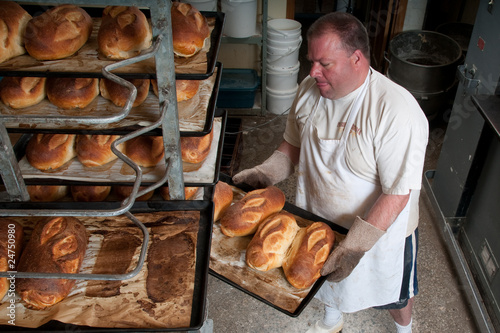Baker Moving Fresh Baked Bread To Cooling Rack