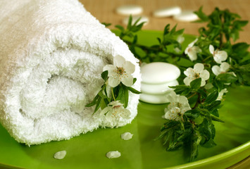spa composition of towel, stones and spring branch with flowers