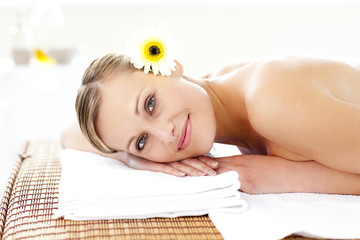 Glowing young woman with flowers in her hair on a massage table