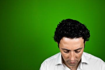 Hombre culpable mirando abajo sobre fondo verde