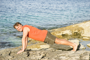 man performing push ups on a rocky beach