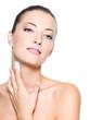 woman applying moisturizer cream on shoulder