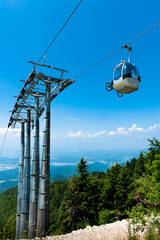 Mountain bike on cable car elevator over alpine forest