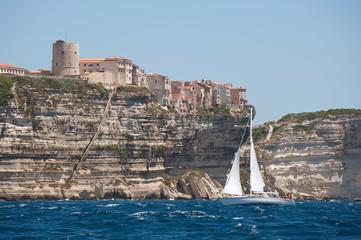 yacht sailing into Bonifacio harbor in Corsica island, France.