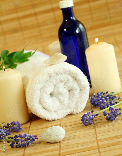 spa composition of towel, flowers and candles