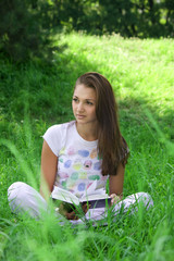 Young girl read a book in the grass
