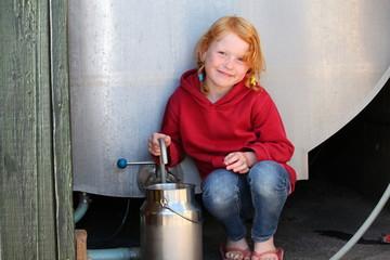 Mädchen füllt Milchkanne aus dem Milchtank