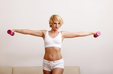 blond woman at home with dumbbell