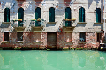 Fassade of old venetian house standing in water