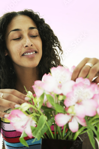Female arranging and smelling flowers
