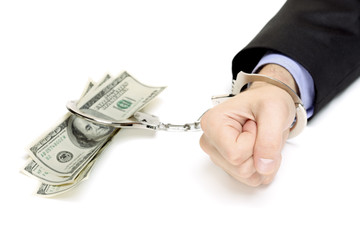 Hand with handcuffs and US dollars isolated against white
