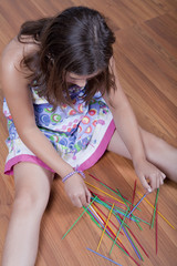 girl playing mikado on the floor