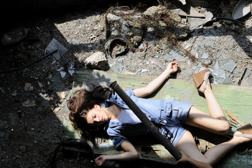 slim young woman simulating suicide in devastated place