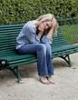 jeune femme triste seule assise sur un banc