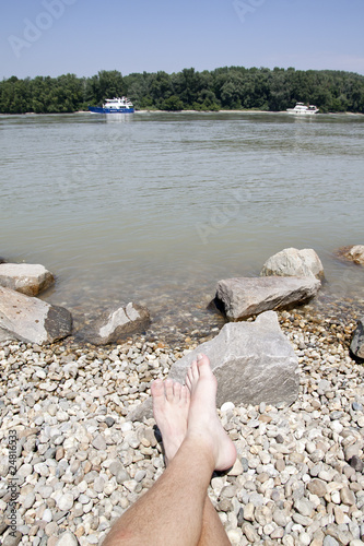 Donau river with boat and feet