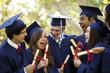 Leinwandbild Motiv Graduating students smiling and laughing with diplomas