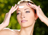 Beautiful woman applying cream on forehead poster