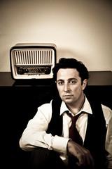 Retro - hombre elegante sentado delante de una radio antigua