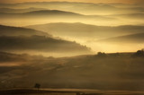 landscape of a beautiful morning with golden mist between hills