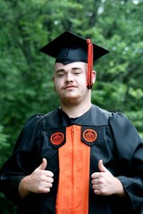 Young man in cap and gown graduating
