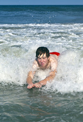 young boy is bodysurfing in the waves
