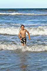 young boy running through the water at the beach