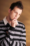 Young atractive pensive man in striped sweater