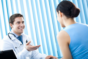Happy doctor and female patient at office