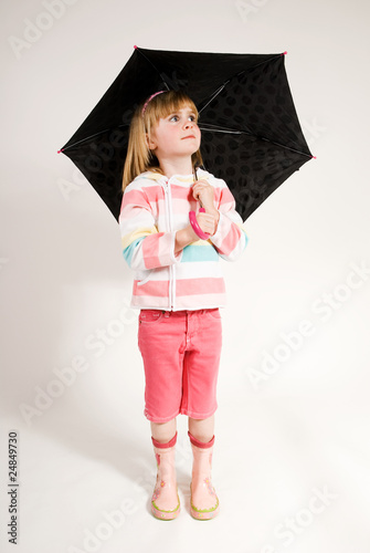 pretty young girl standing with umbrella looking up