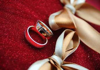 Two wedding rings on a red pillow