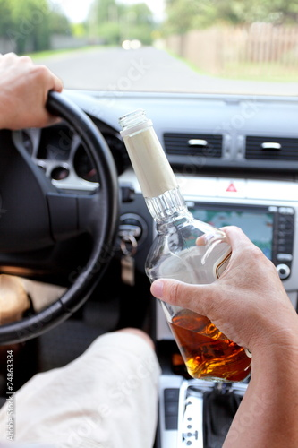 Drunk driver on a rural road with a bottle of alcohol in hand